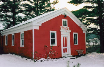 Small red building with white door and windows