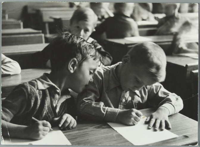 boy looking at paper of boy sitting next to him
