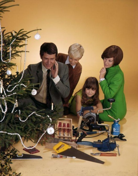 Family around a Christmas tree, with presents