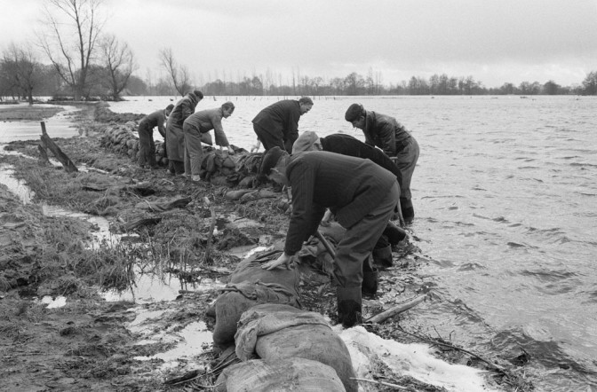 People lying sandbags near a river