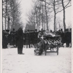 a coffin covered by flowers is surrounded by a group of mourners in black attire