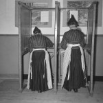 Women in traditional costume in a voting booth.