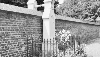 Two grave markers on opposite sides of a wall, holding hands above the wall