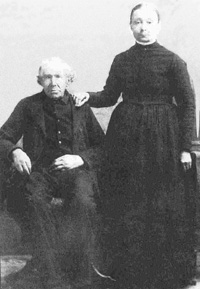 Portrait of an old man sitting down and a younger woman standing next to him