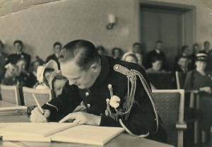 Man in uniform signing a document