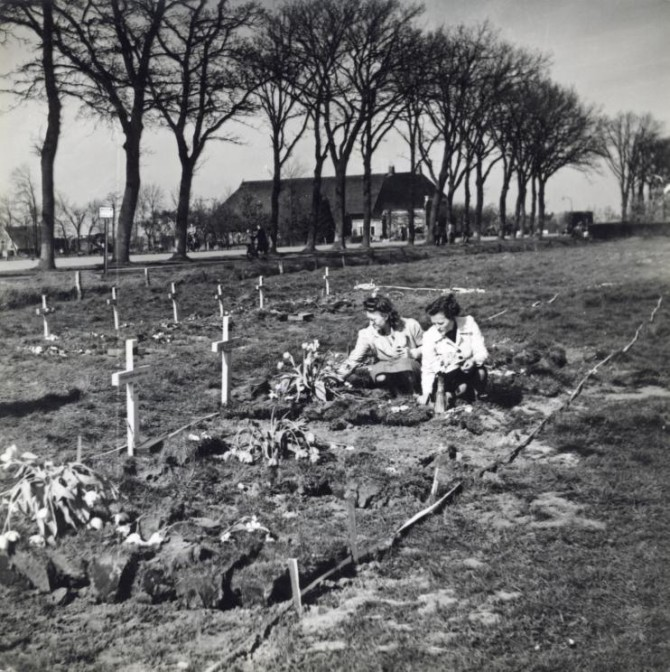 Dutch girls laying flowers on the graves of a temporary graveyard for killed Canadian soldiers. Edderwolde, The Netherlands, 1945.