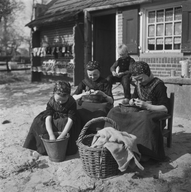 Children peeling potatoes while wearing traditional costumes, 1946