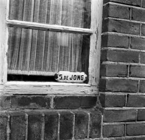 G de Jong name tag in a window
