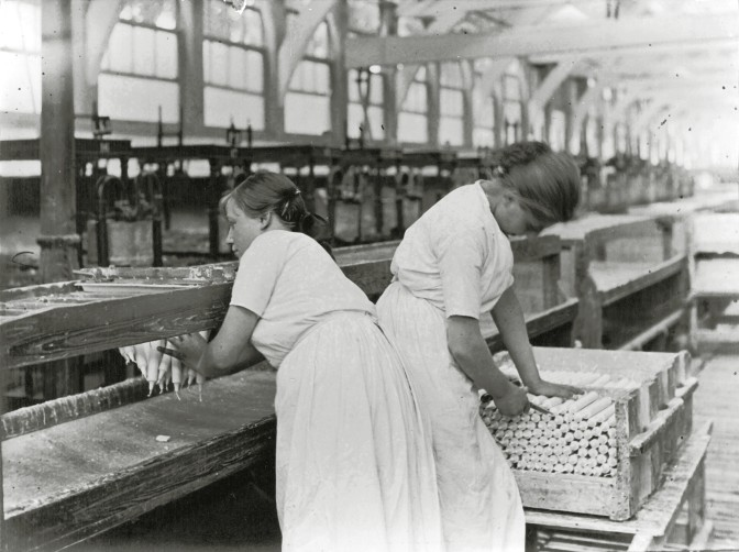 two women packing candles in an assembly line