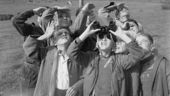 Boys looking up with binoculars