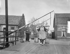woman carrying milk on a yoke over her shoulders across a toll bridge