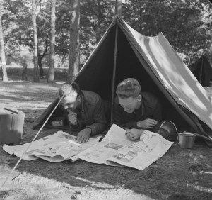 two soldiers reading a newspaper in front of their tents