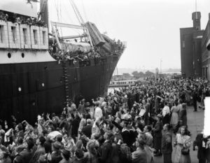 ship in port with passengers flocking to the side