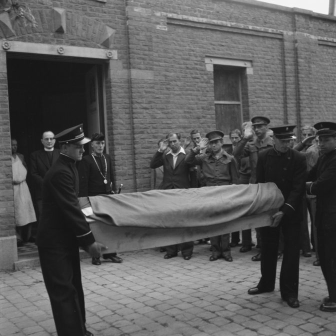 Coffin with pall carried outside