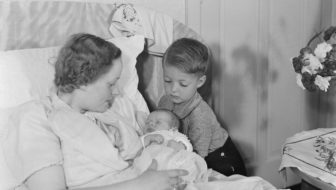 mother in bed with a baby, with the brother looking on