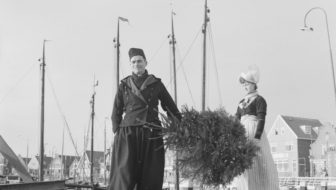 Couple in traditional costume carrying a Christmas tree