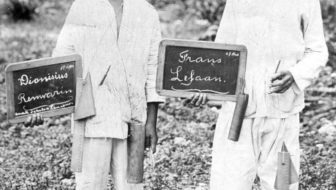 two boys showing blackboards with their names