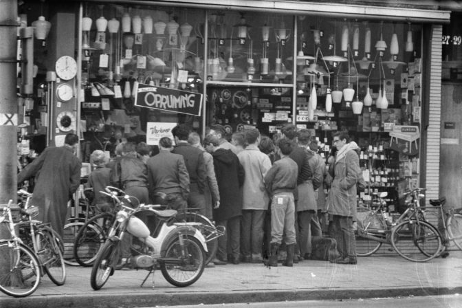 people pressed against a shop window