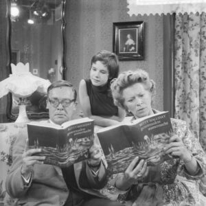people reading a book, looking surprised